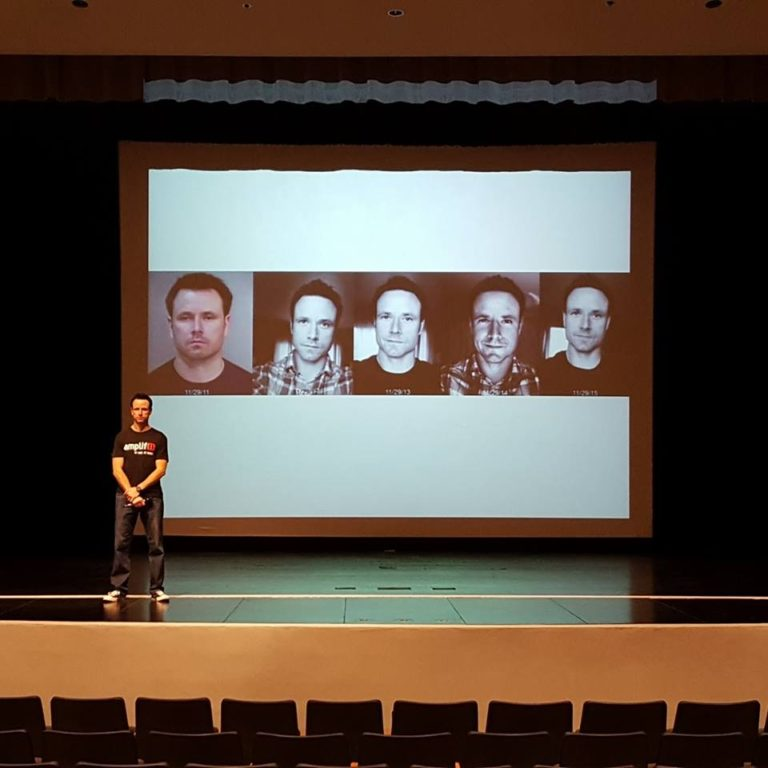 On stage performing a speaking engagement at Apache Junction High School